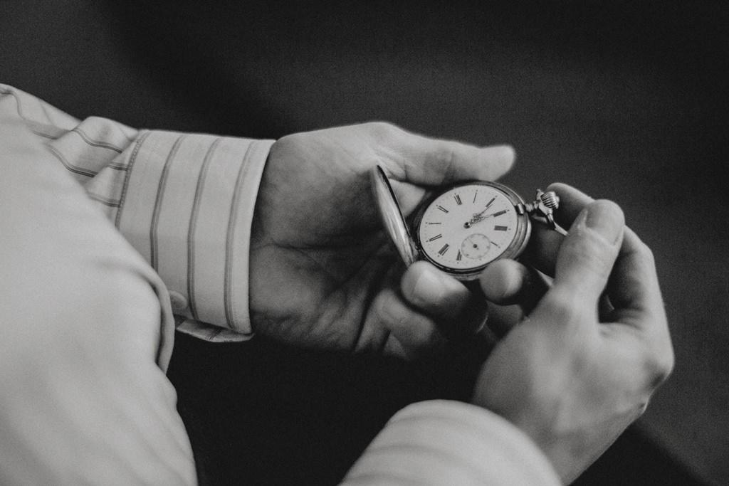 Bräutigam hält eine antike Taschenuhr in der Hand