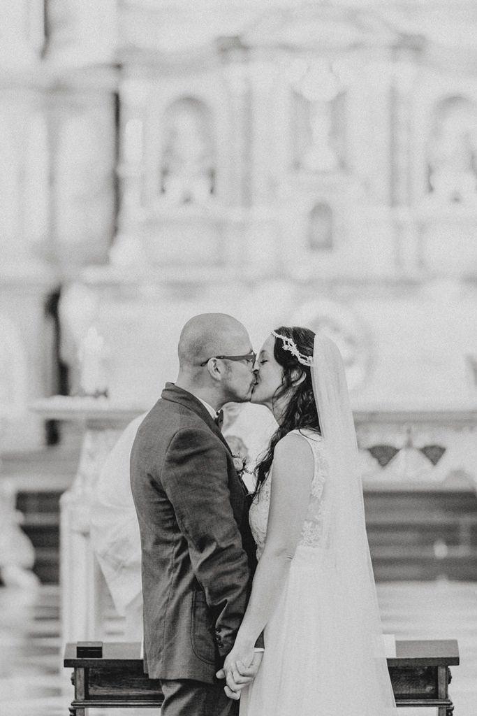 das Brautpaar küsst sich in der Kirche