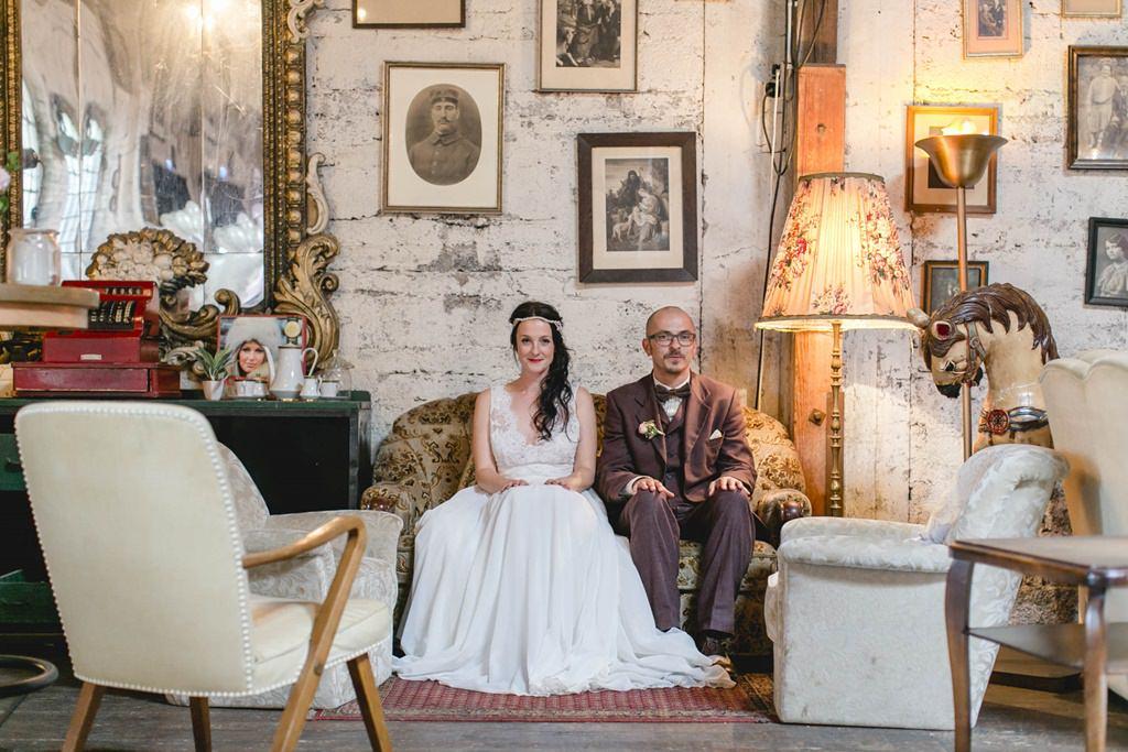 Foto von Braut und Bräutigam auf einer Couch umgeben von Bilderrahmen