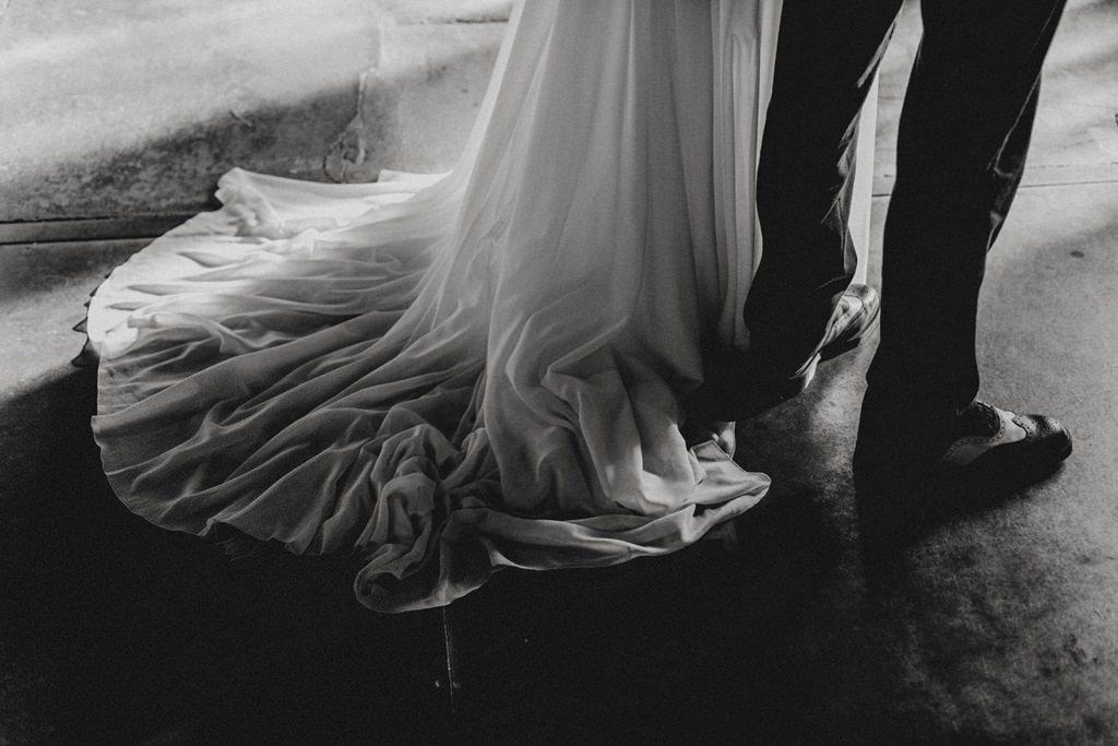 Schleppe der Braut und Schuhe des Bräutigams