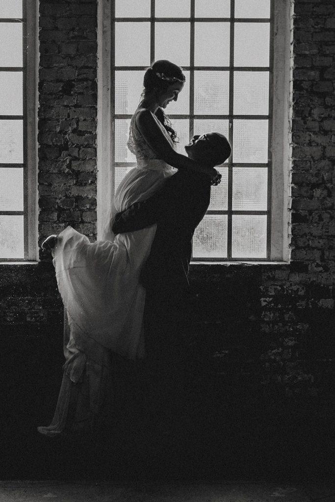 Bräutigam hebt die Braut vor einem Fenster hoch