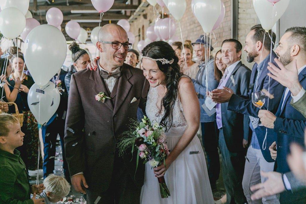 das strahlende Brautpaar wird von den Gästen mit Luftballons empfangen