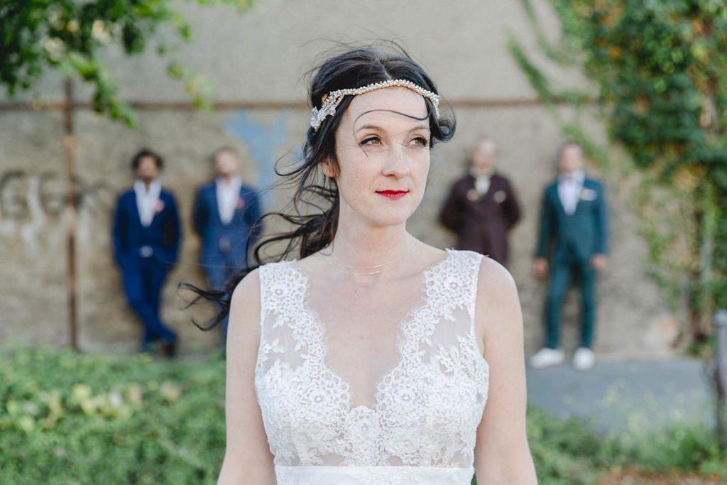 Braut im Vordergrund, Bräutigam mit Trauzeugen im Hintergrund