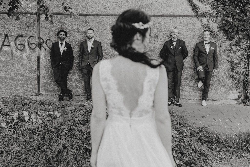 Braut von hinten im Vordergrund, Bräutigam mit Trauzeugen im Hintergrund