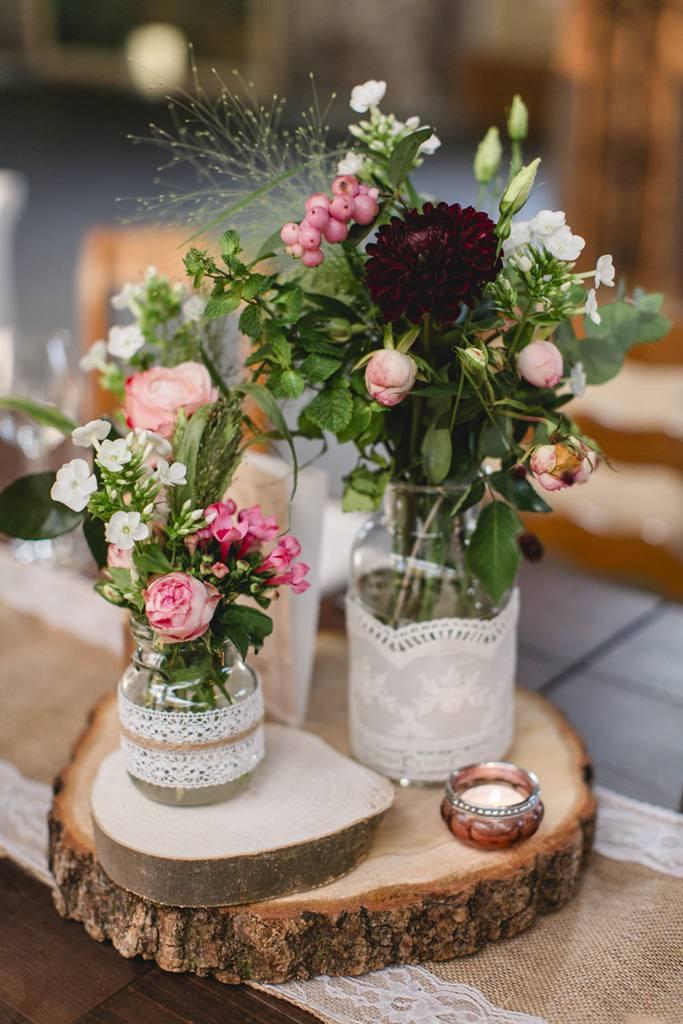 Hochzeitstischdeko mit Blumen und Baumplatte