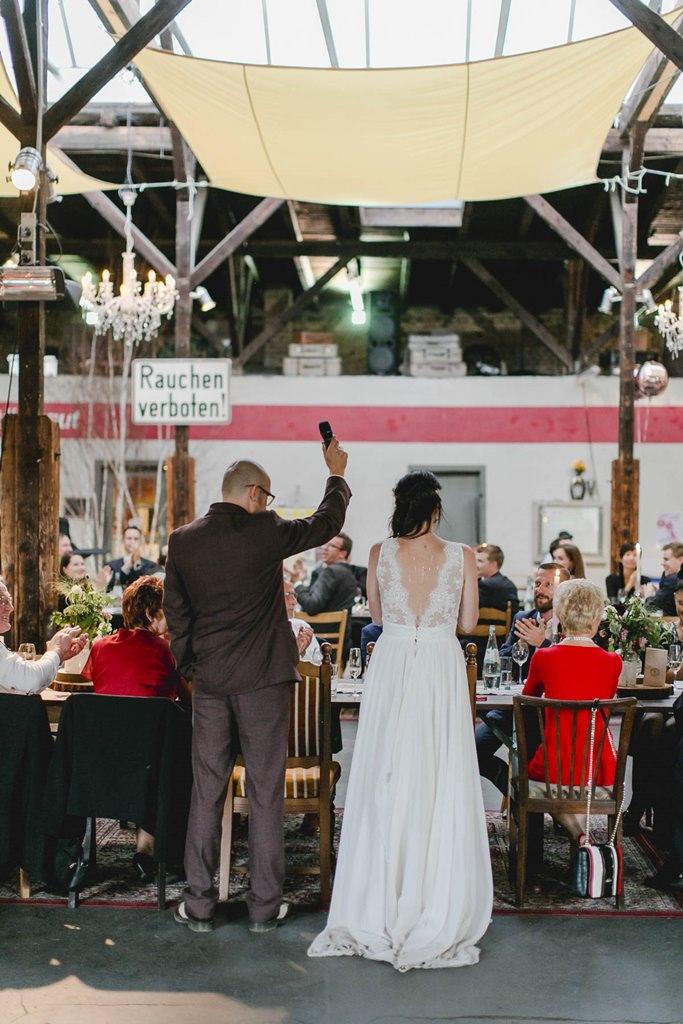 Braut und Bräutigam von hinten während der Rede des Bräutigams