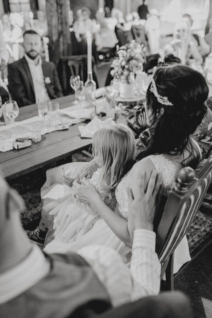 Braut und Bräutigam mit ihrer Tochter am Hochzeitstisch