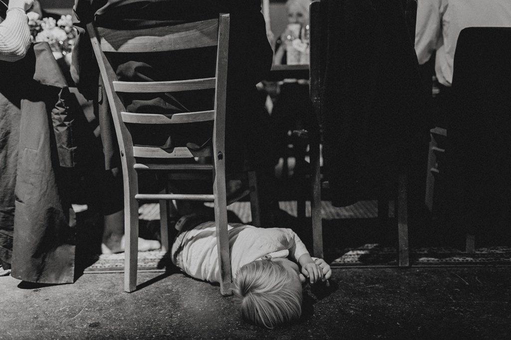 ein müdes Kind schläft unter einem Stuhl