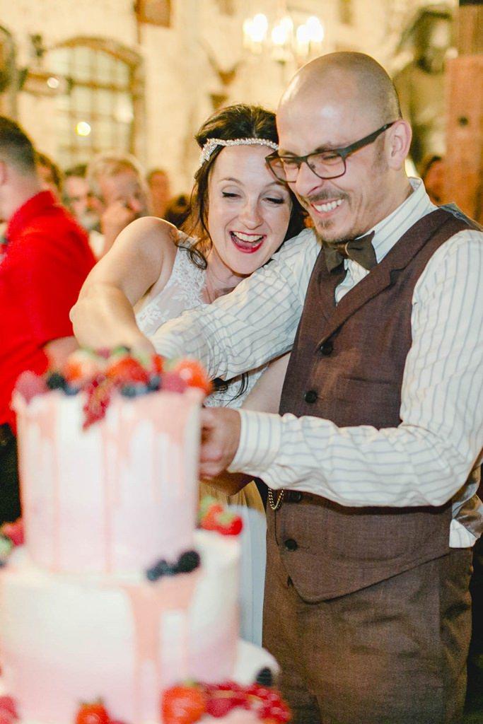 das glückliche Brautpaar schneidet die Hochzeitstorte an