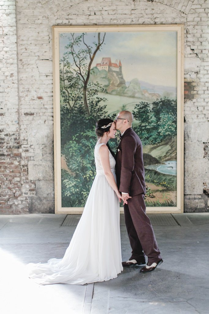 Hochzeitspaar küsst sich vor großem Gemälde