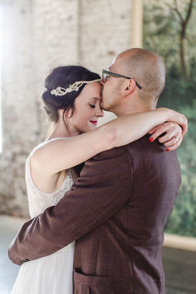 Bräutigam küsst Braut zärtlich auf die Stirn