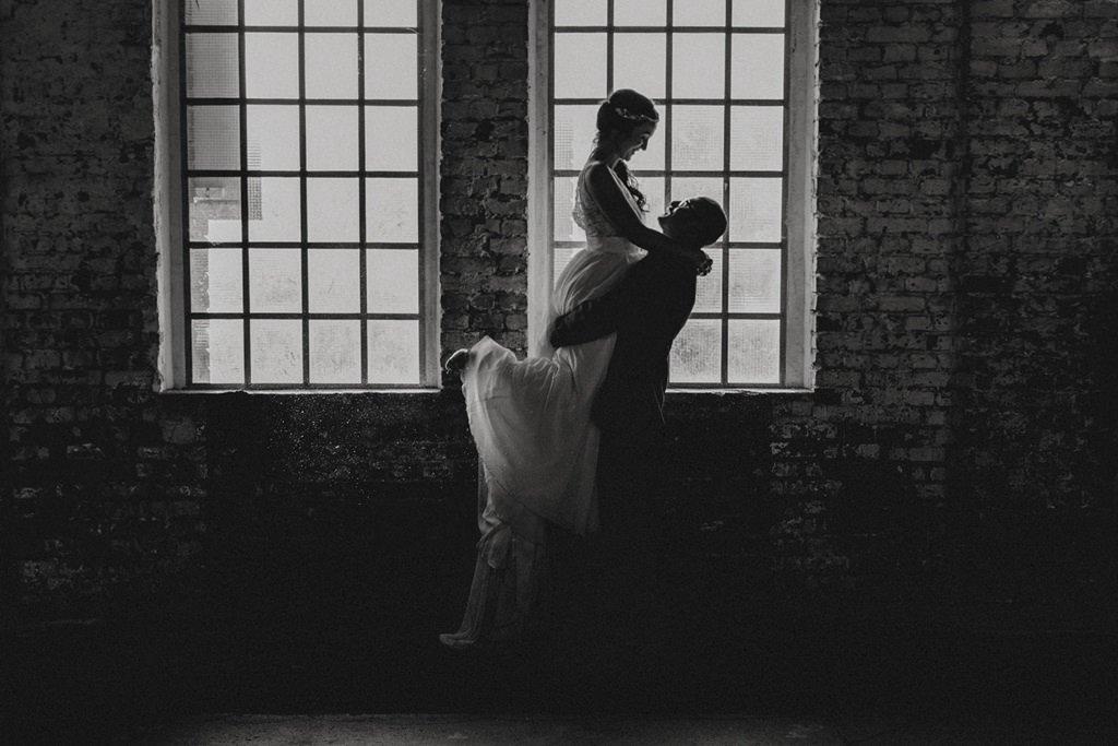 schwarz-weiss Bild von Bräutigam, der die Braut vor einem Fenster hochhebt