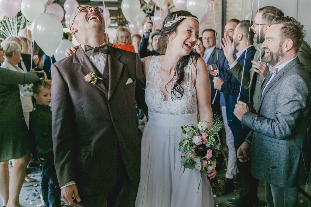 glückliches Brautpaar schreitet durch das Gästespalier