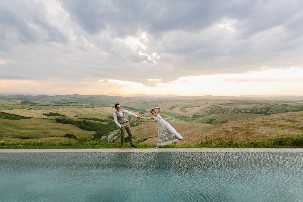 Hochzeitsfotoidee: Braut und Bräutigam stehen zwischen einem Pool und der toskanischen Landschaft