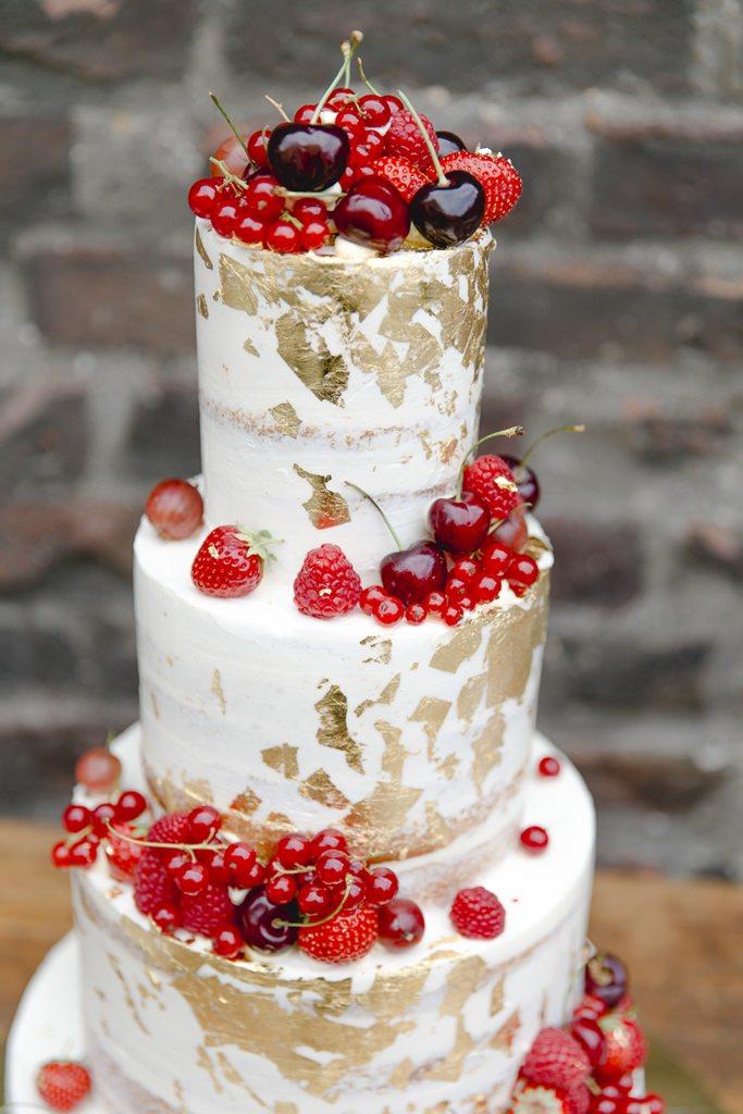 weiße Hochzeitstorte mit Goldglitter und roten Früchten
