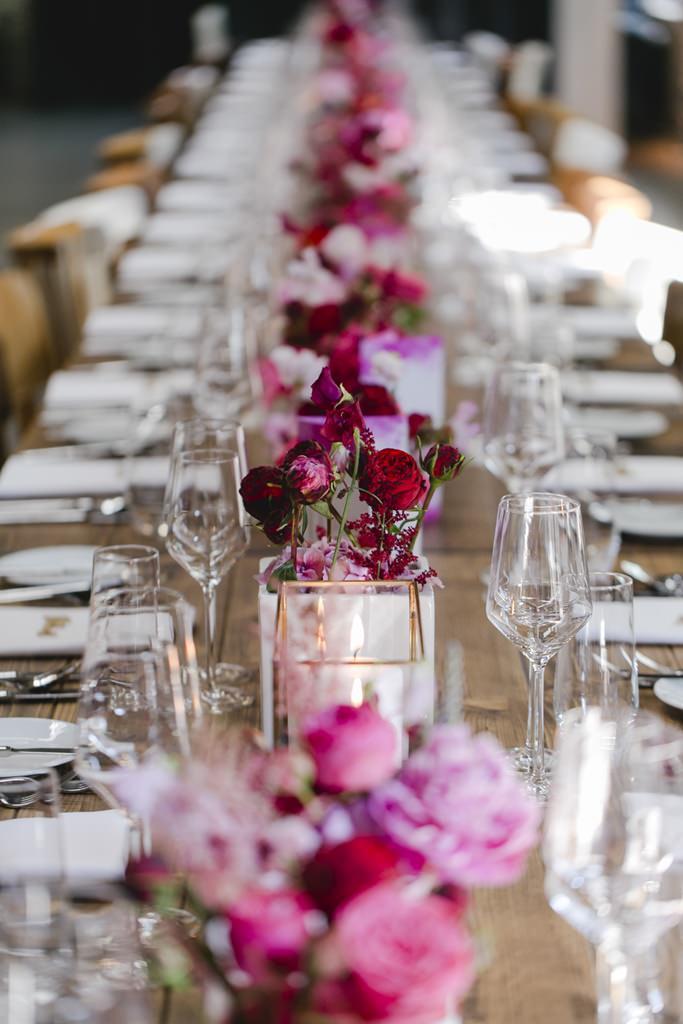 hochzeitstischdeko mit Blumen in Rot, Rosa und Pink