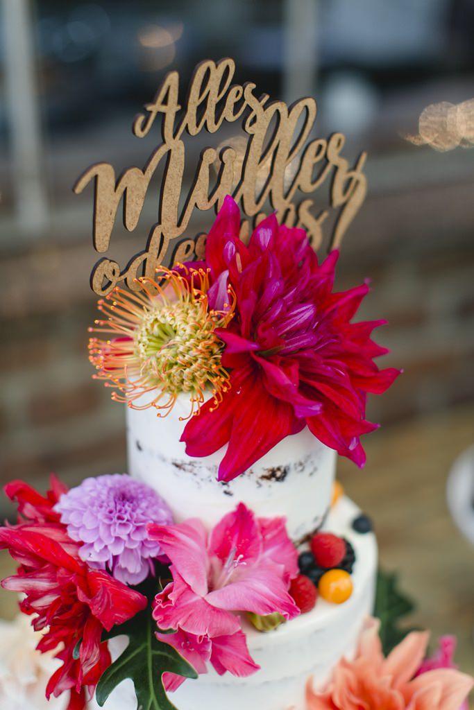 Hochzeitsfoto von einer Hochzeitstorte mit Cake Topper und bunten Blumen