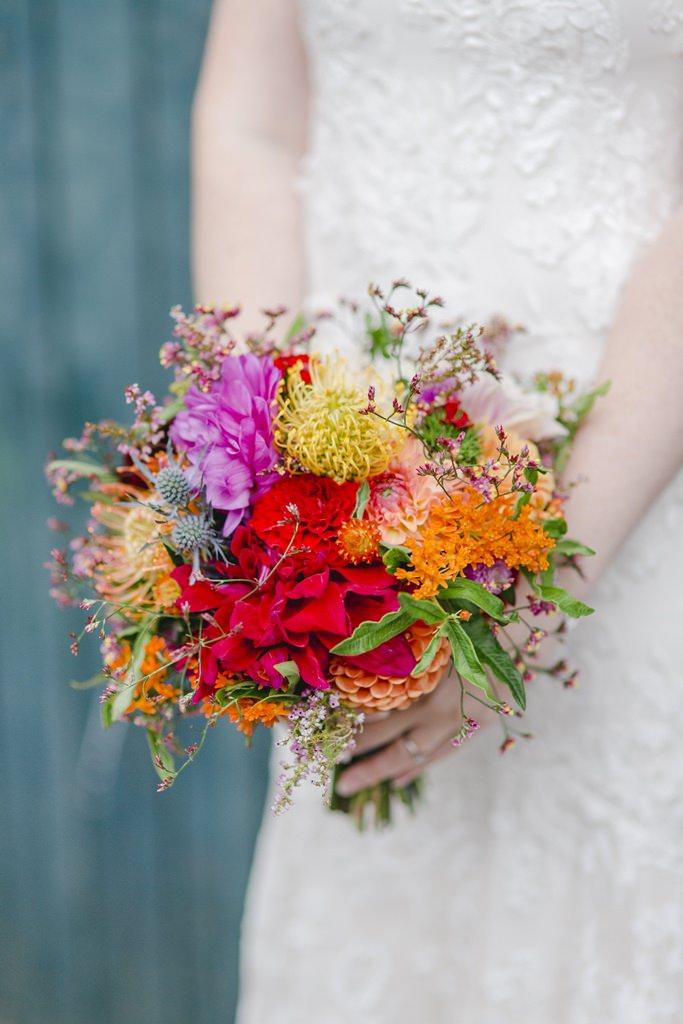 Hochzeitsfoto von einem bunten Brautstrauss in Rot, Gelb und Orange