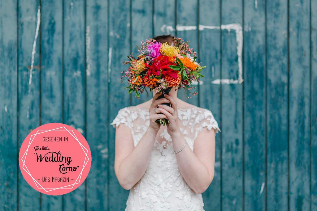 Hochzeitsfoto einer Braut, die sich einen bunten Brautstrauss vor ihr Gesicht hält