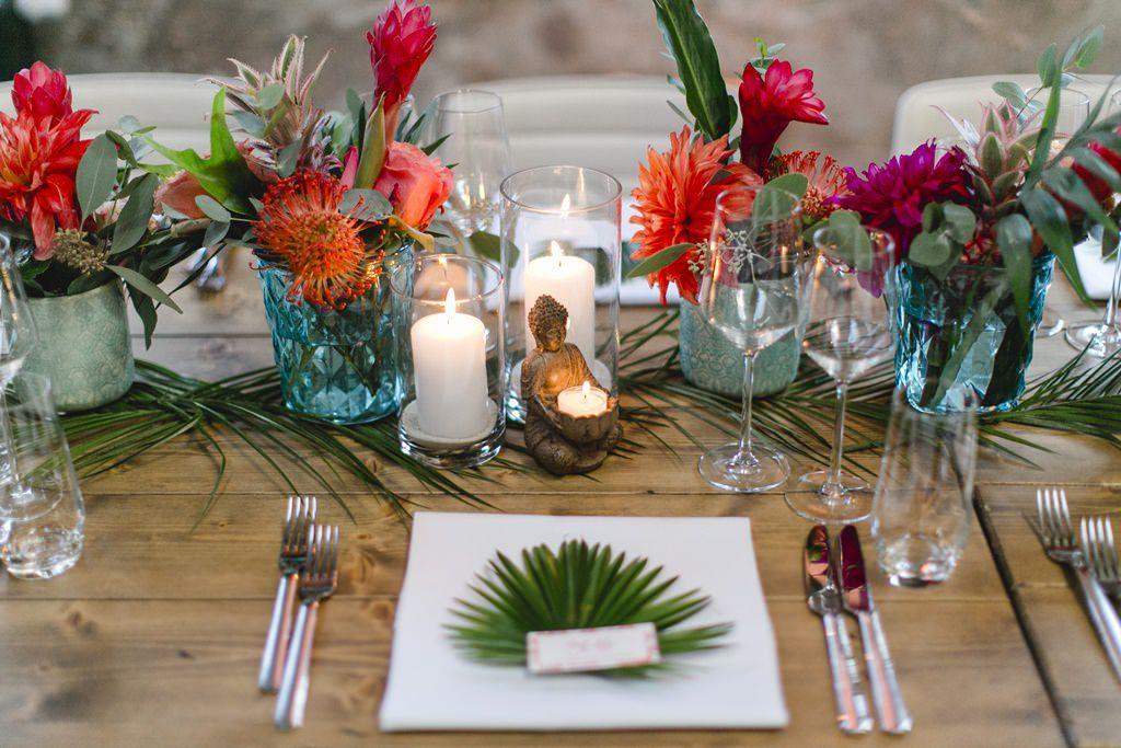 Tischdeko mit tropischen Blumen und Palmenblatt