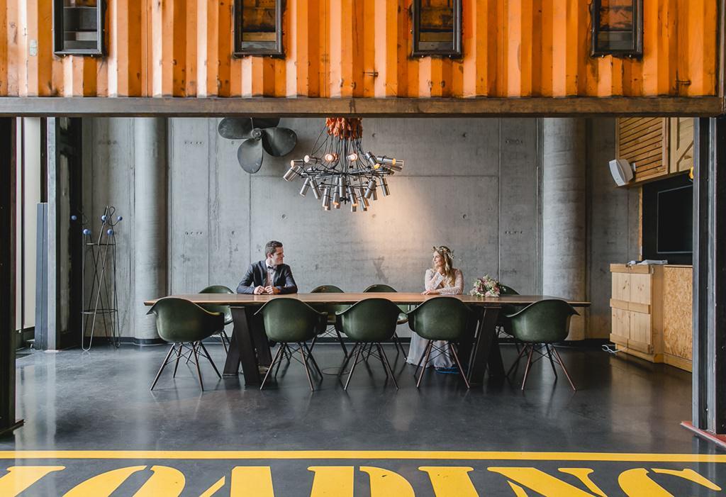Braut und Bräutigam sitzen an einem Tisch in einer Halle | Foto aufgenommen beim Hochzeitsfotografie Workshop von Fotografin Hanna Witte für den bpp