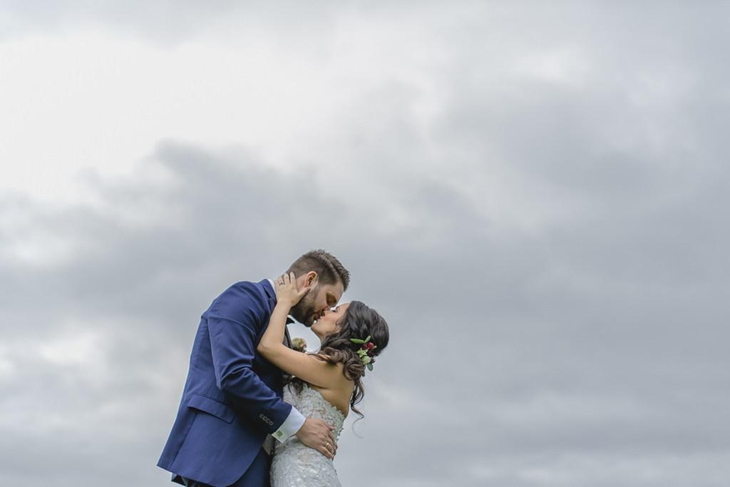 Braut und Bräutigam küssen sich mit dem Himmel im Hintergrund