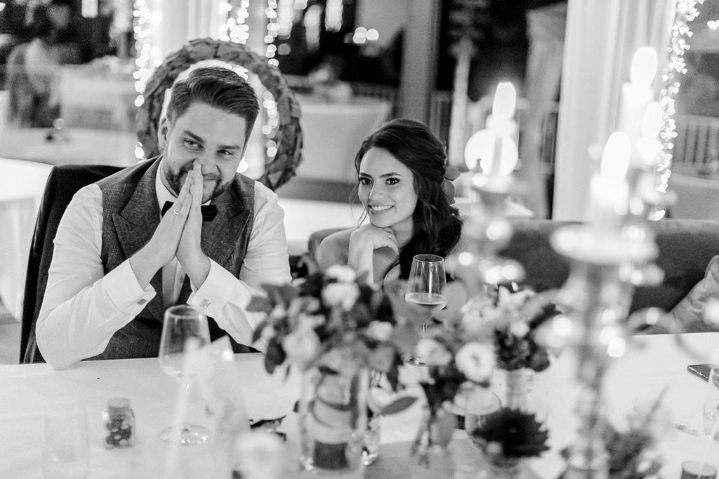 Braut und Bräutigam hören sich bei der Hochzeitsfeier eine Rede an