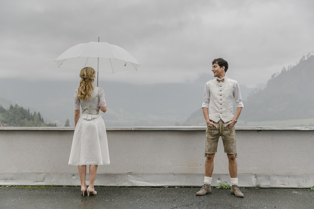 Braut und Bräutigam stehen in festlicher Tracht auf einer Brücke