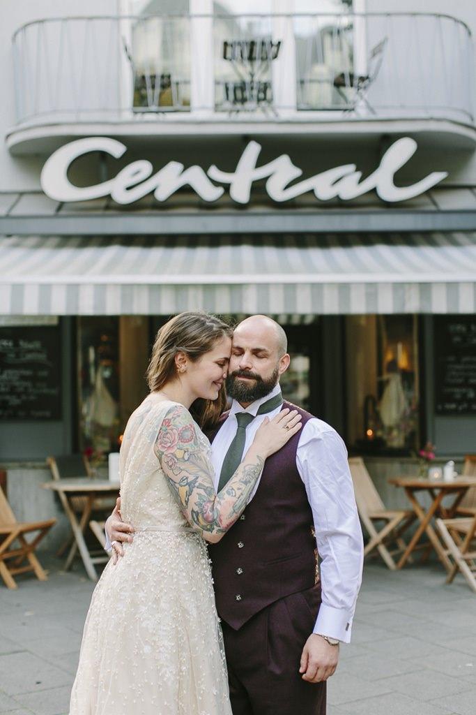 Braut und Bräutigam stehen Arm in Arm vor einem Café