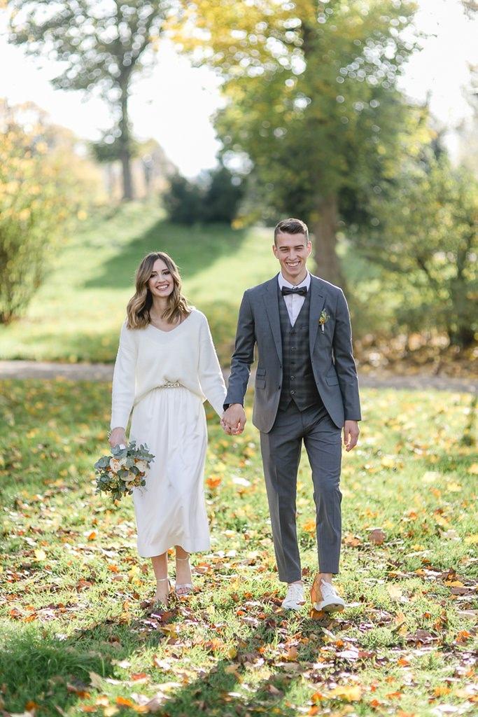 Braut und Bräutigam laufen Hand in Hand durch einen Park
