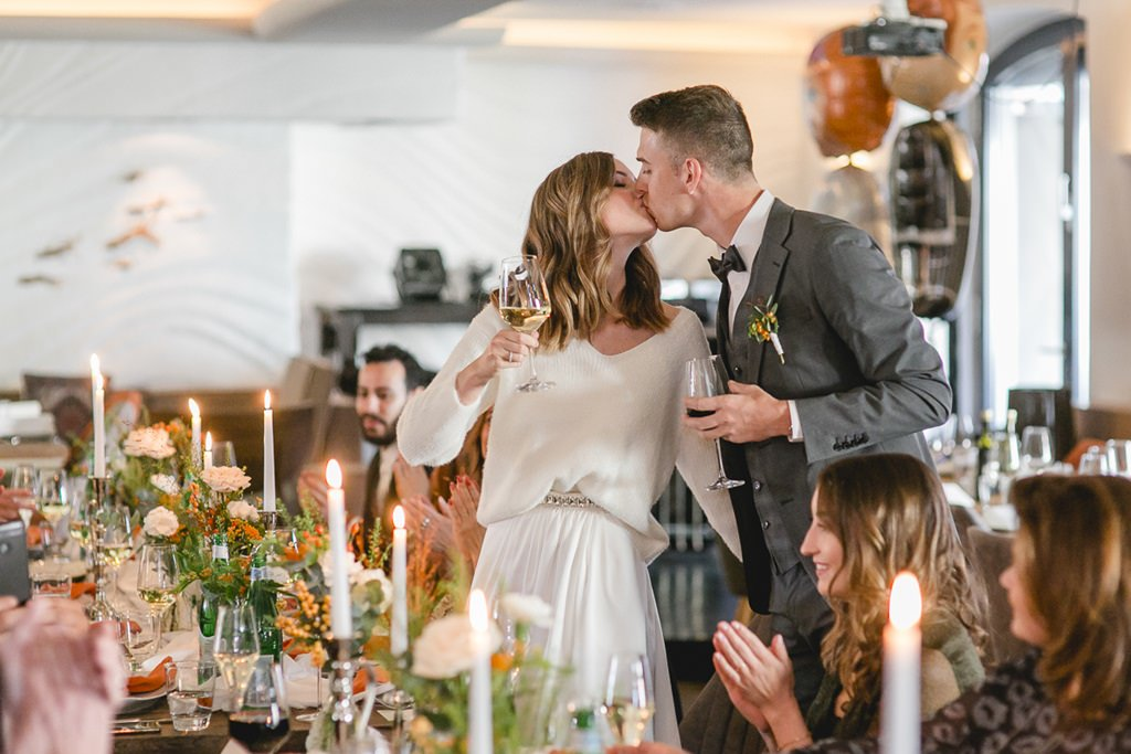 Braut und Bräutigam küssen sich beim Anstoßen