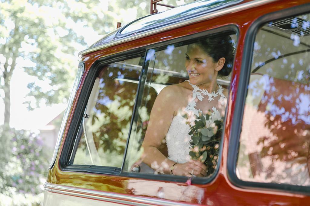 die Braut fährt in einem roten Auto vor