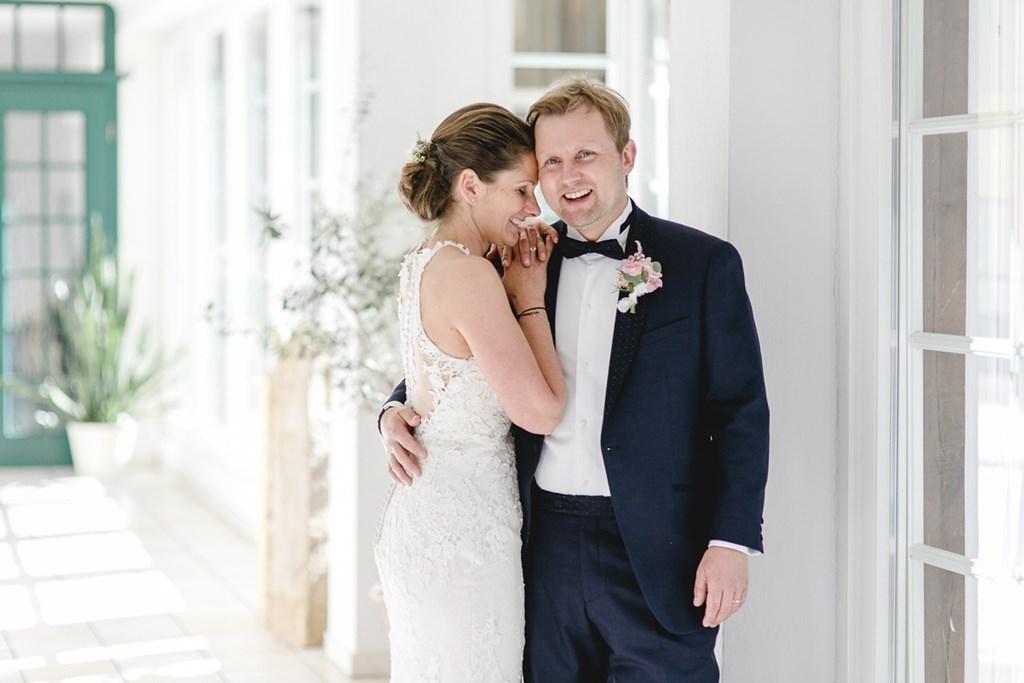 der glückliche Bräutigam hält eine strahlende Braut im Arm