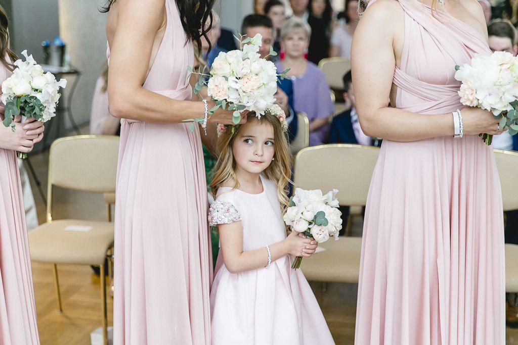 kleines Blumenmädchen zwischen den Brautjungfern