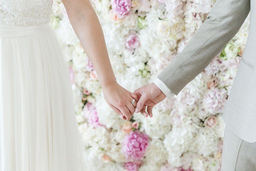 Braut und Bräutigam halten sich vor einer Blumenwand an den Händen