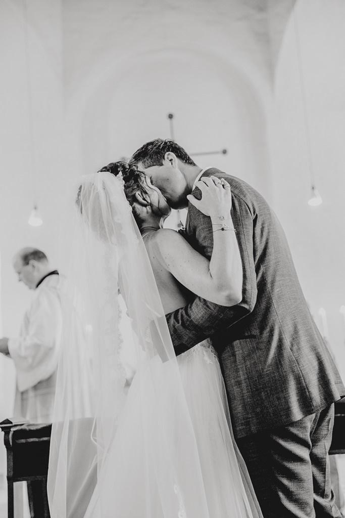 das Hochzeitspaar küsst sich nach der kirchlichen Trauung