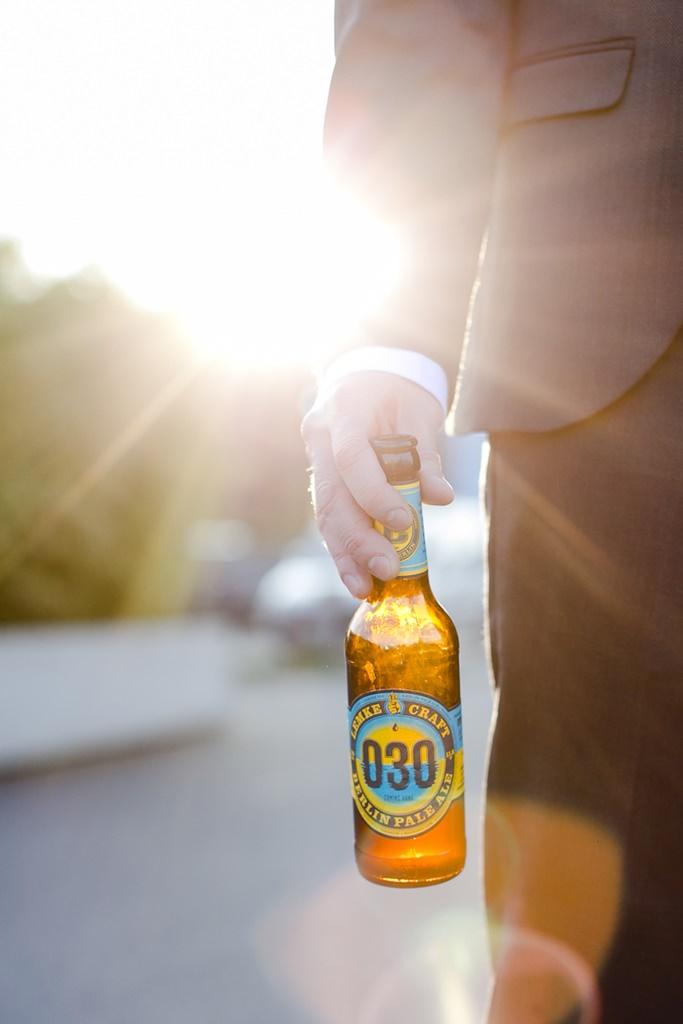 der Bräutigam hält entspannt ein Bier in der Hand