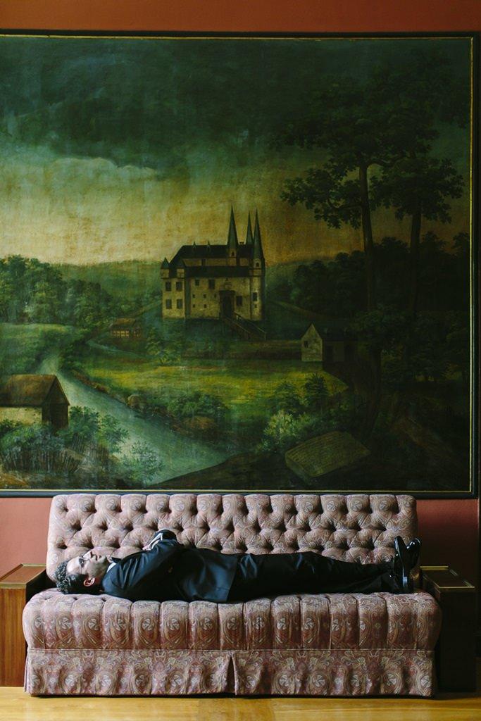 der Bräutigam wartet auf einem alten Sofa