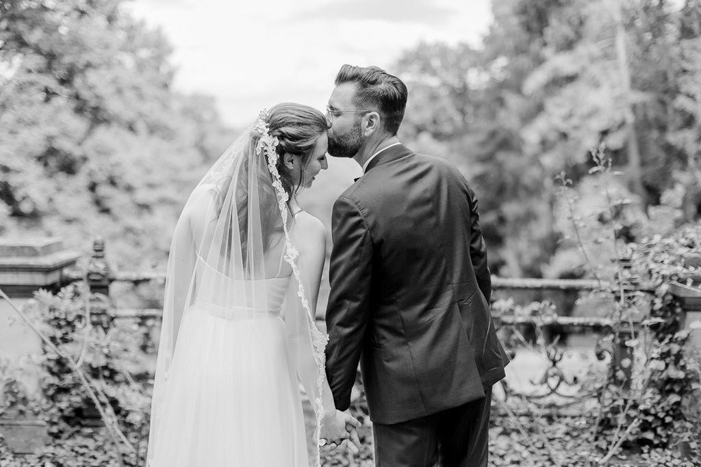 der Bräutigam küsst die Braut liebevoll auf die Stirn