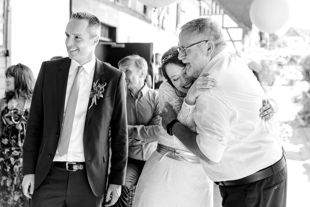 die Braut wird von ihrem Vater nach der Trauung gedrückt