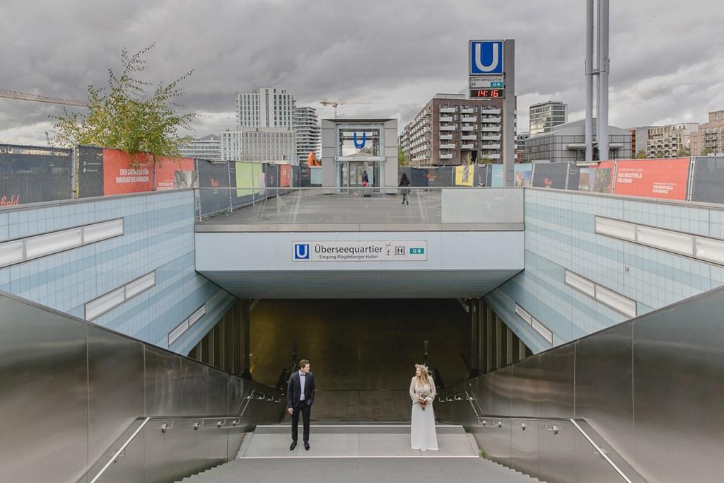 Braut und Bräutigam stehen auf einer Treppe zur U-Bahn