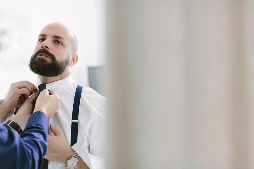 der Bräutigam bekommt seine Krawatte gebunden