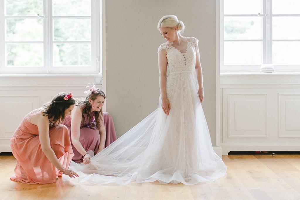 Brautjungfern richten den Schleier der Braut