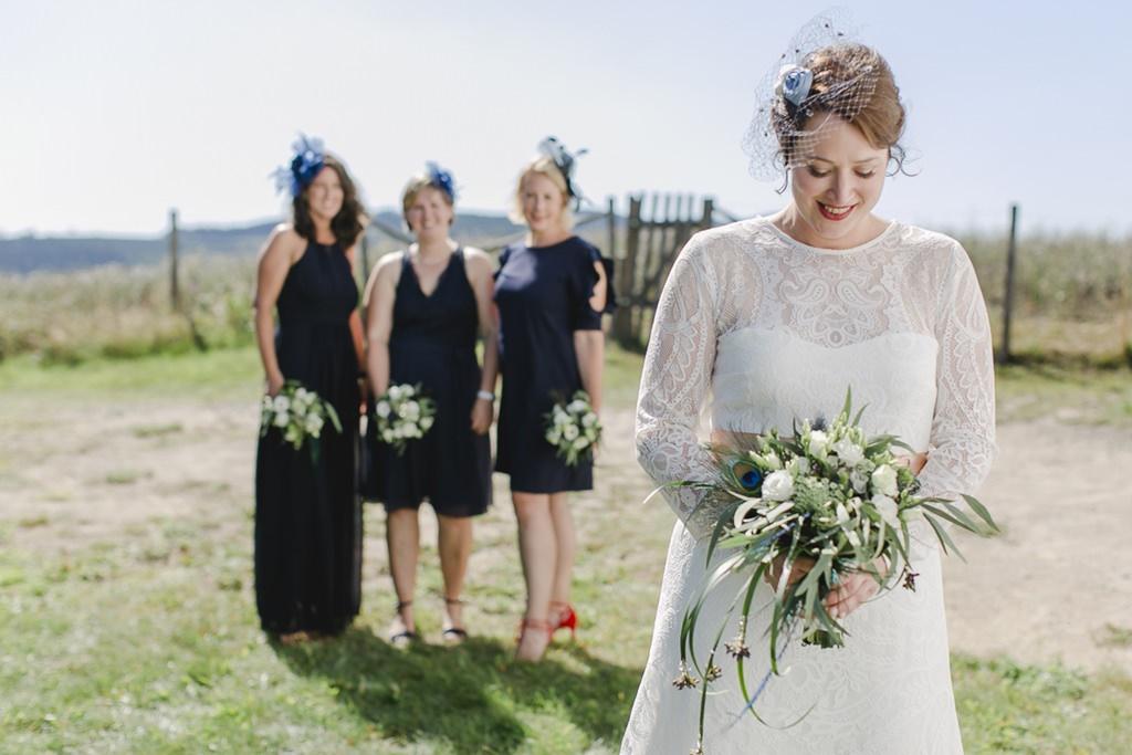 die Braut steht vor ihren Brautjungfern und hält ihren Brautstrauß in der Hand