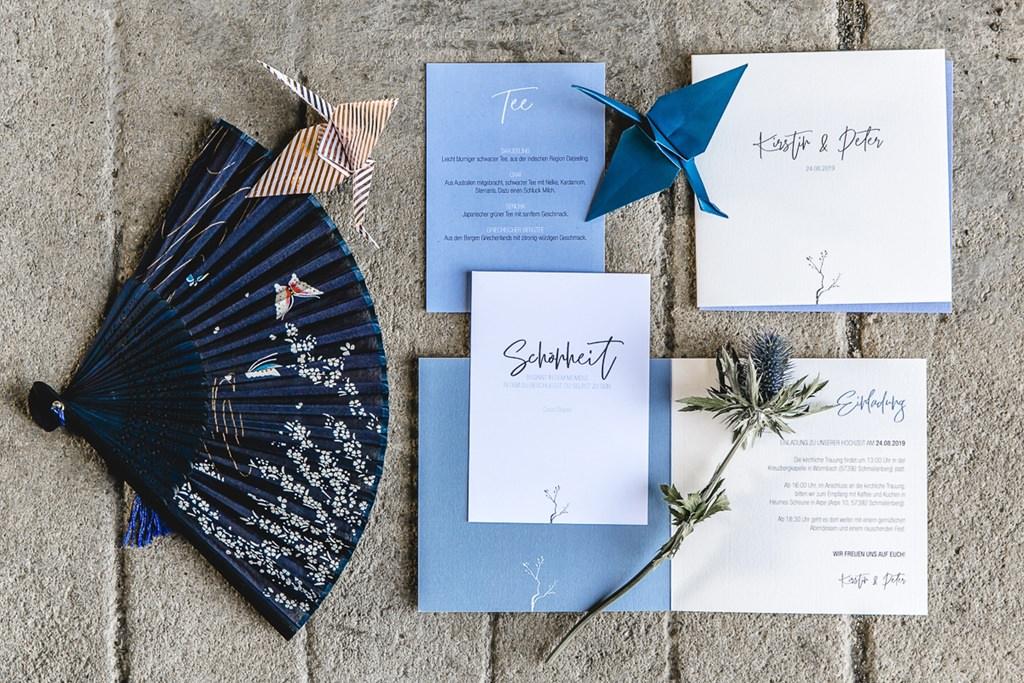 Hochzeitspapeterie in Hellblau liegt neben einer Distel, Origami und einem Fächer