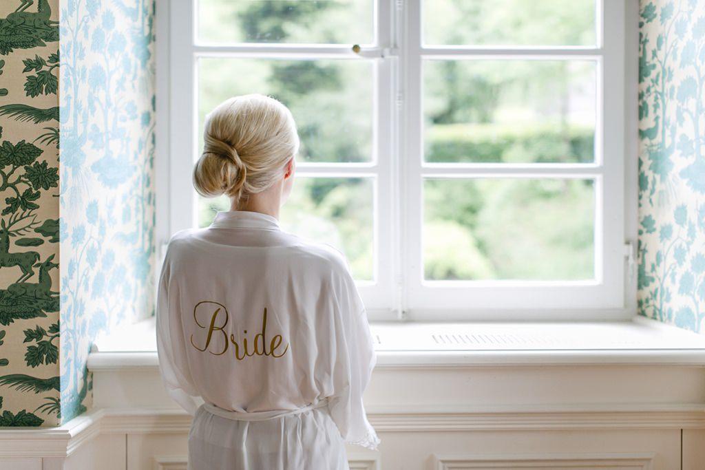 die Braut trägt einen Bademantel mit der Aufschrift Bride