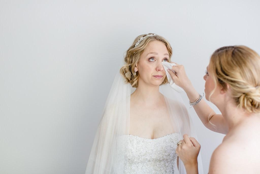 eine Freundin wischt der Braut die Tränen weg