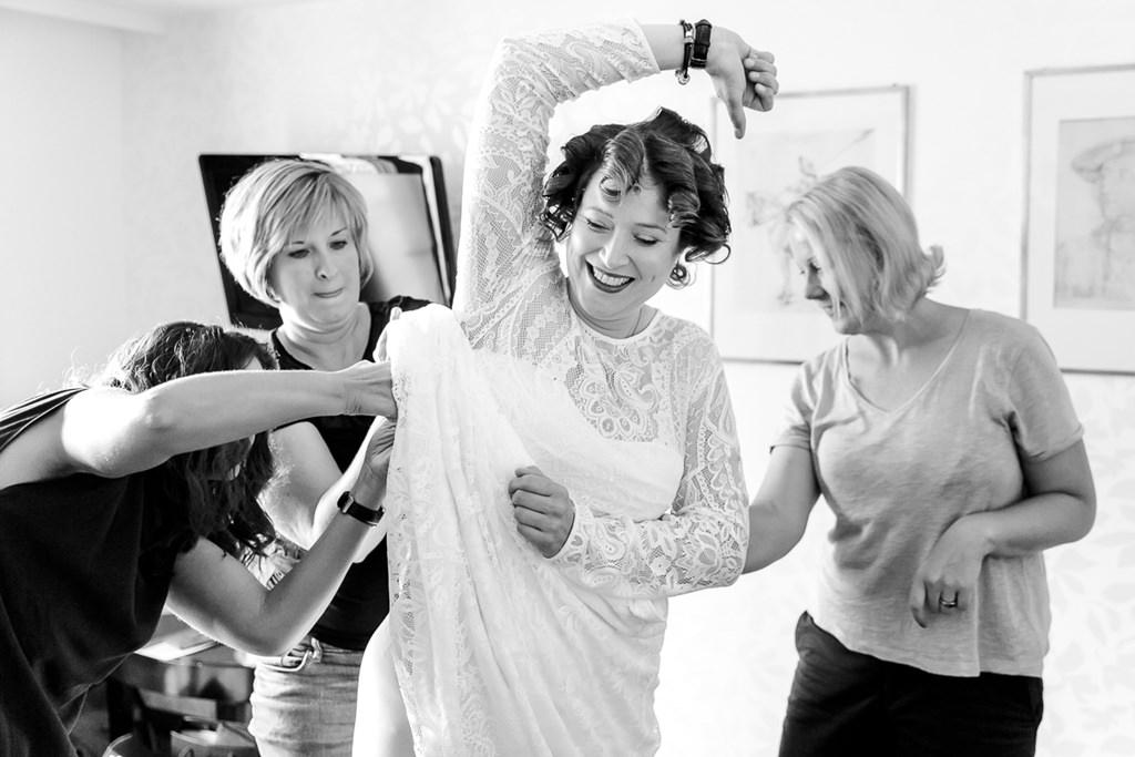 Freundinnen helfen der Braut beim Getting Ready ihr Brautkleid anzuziehen
