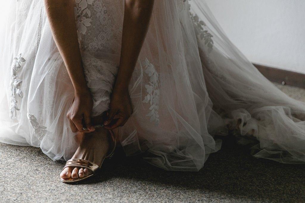die Braut zieht beim Getting Ready ihre Schuhe an