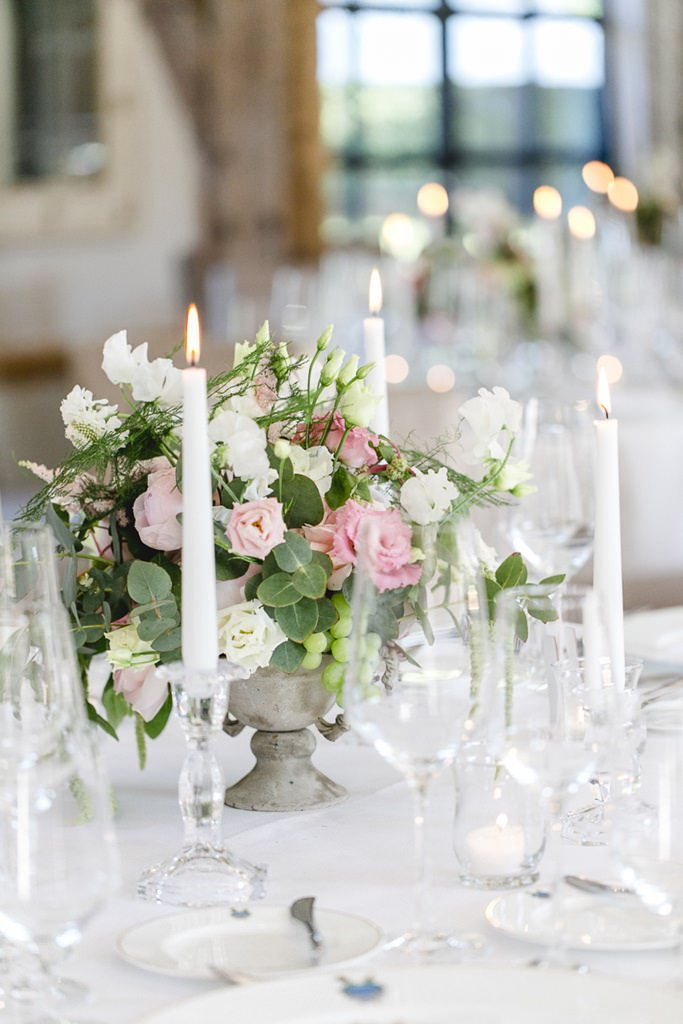Hochzeitstischdeko mit weißen Kerzen und Rosen in Weiß und Rosa
